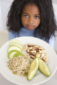 Young girl in kitchen eating rice fruit and nuts — Stock Photo