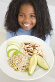 Young girl in kitchen eating rice fruit and nuts smiling — Stock Photo