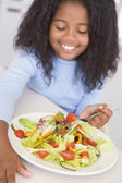 Young girl in kitchen eating salad smiling — Stock Photo