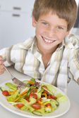Young boy in kitchen eating salad smiling — Stock Photo