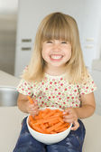 Young girl in kitchen eating carrot sticks smiling — Stock fotografie