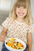 Young girl in kitchen eating bowl of fruit smiling — Stock Photo