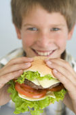 Young boy eating cheeseburger smiling — Stock Photo
