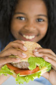 Young girl eating cheeseburger smiling — Stock Photo