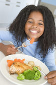 Young girl in kitchen eating chicken and vegetables smiling — Stock Photo