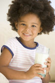 Young girl indoors drinking milk smiling — Stock Photo