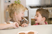 Two young boys in kitchen eating cookies smiling — Stock Photo