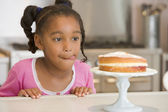 Young girl in kitchen looking at cake on counter — Stock Photo