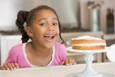 Young girl in kitchen looking at cake on counter smiling — Stock Photo