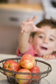 Young boy in kitchen getting apple off counter — Stock Photo
