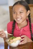 Young girl in dining room eating Chinese food smiling — Стоковое фото