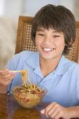 Jonge jongen in de eetzaal eten chinees eten glimlachen — Stok fotoğraf