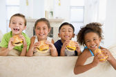Four young children eating cheeseburgers in living room smiling — Stok fotoğraf