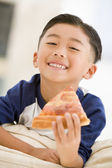 Young boy eating pizza slice in living room smiling — Stock Photo