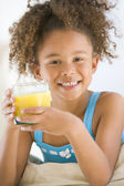 Young girl drinking orange juice in living room smiling — Stock Photo