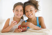 Two young girls eating strawberries in living room smiling — Stock Photo
