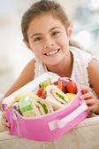 Young girl holding packed lunch in living room smiling — Stock Photo