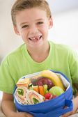 Young boy holding packed lunch in living room smiling — Stock Photo
