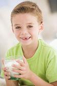 Mladík uvnitř pití mléka s úsměvem — Stock fotografie