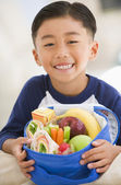 Young boy indoors with packed lunch smiling — Stock Photo