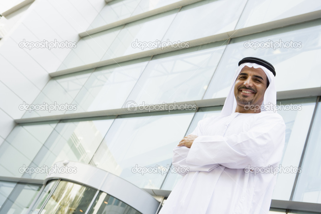 A Middle Eastern businessman standing outside an office block — Stock Photo #4760113