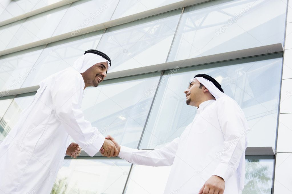 Two Middle Eastern businessmen shaking hands outside an office b — Stock Photo #4760147