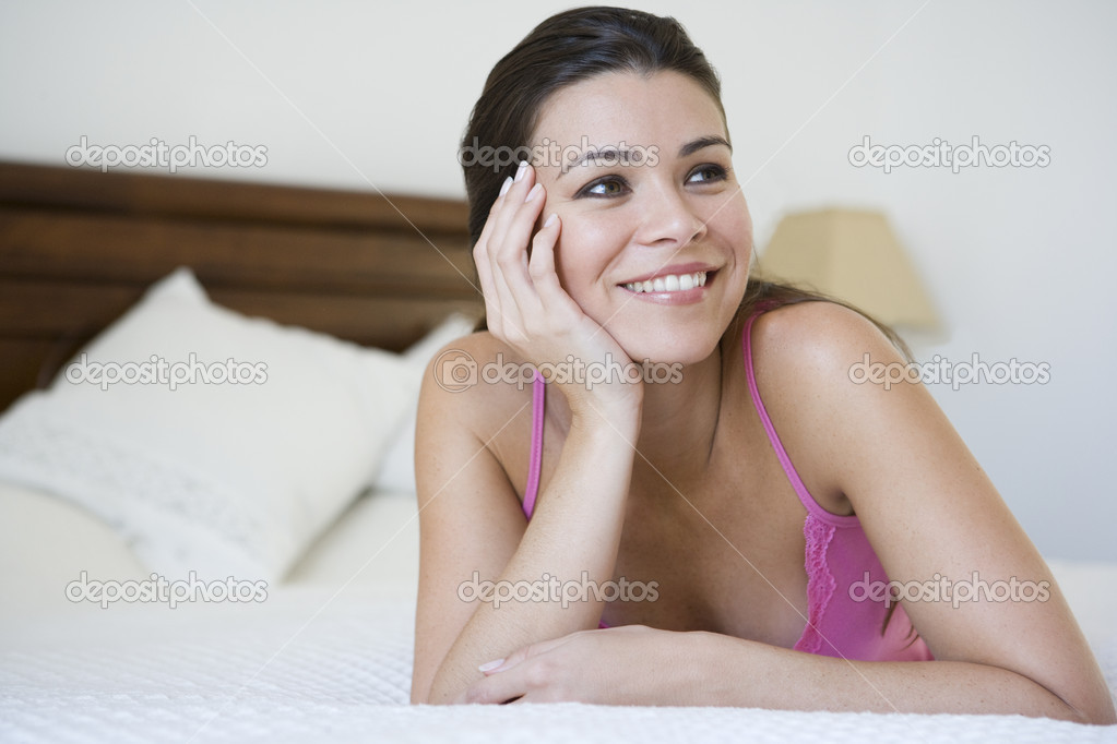 Middle Eastern woman lying on a bed - Stock Image