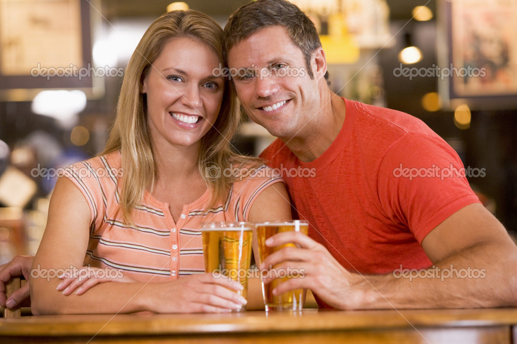 Happy young couple having beers at a bar  Stock Photo #4761035