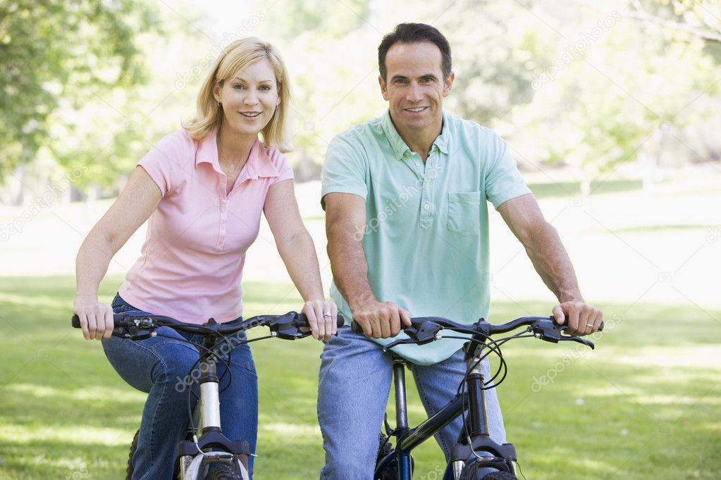 Couple on bikes outdoors smiling — Stock Photo #4764018