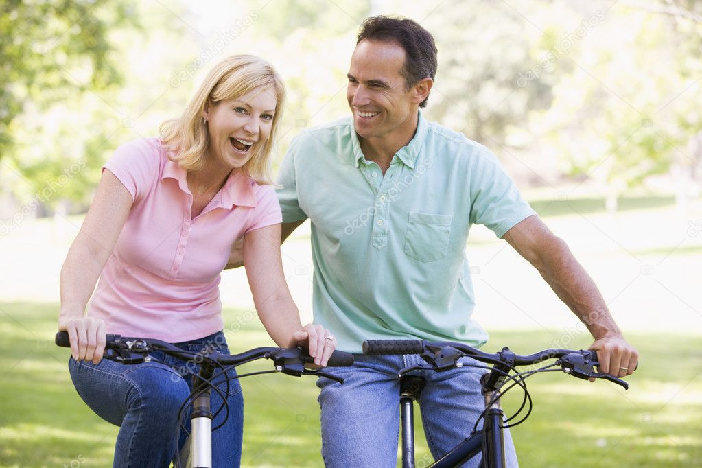 Couple on bikes outdoors smiling — Stock Photo #4764019