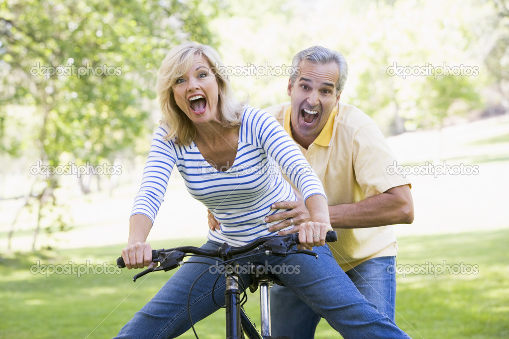 Couple on bike outdoors smiling and acting scared — Stock Photo #4764046