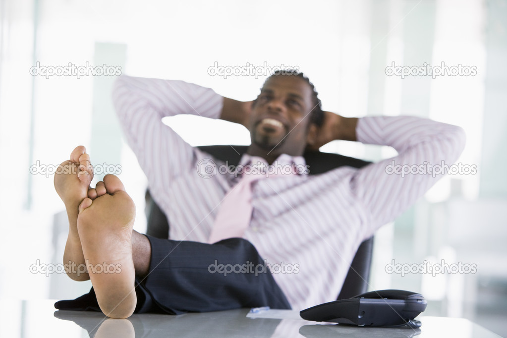 Businessman Sitting In Office With Feet On Desk Relaxing