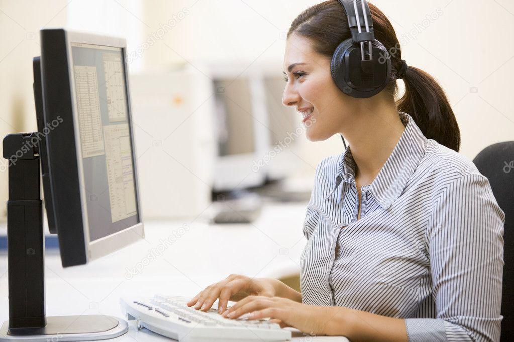 Woman wearing headphones in computer room typing