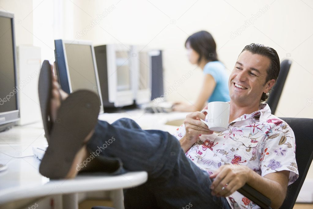 Man in computer room with feet up drinking coffee and smiling — Stock Photo #4767013