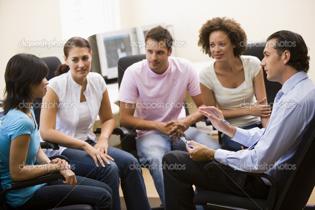Man giving lecture to four in computer room — Stock Photo #4767161