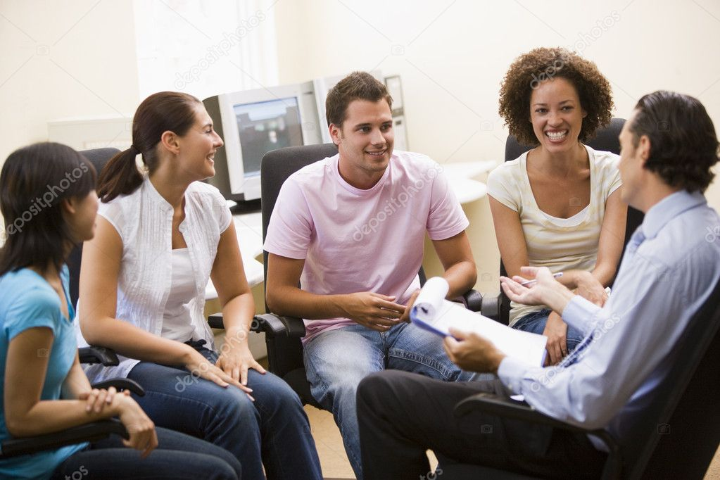 Man giving lecture to four in computer room — Stock Photo #4767162