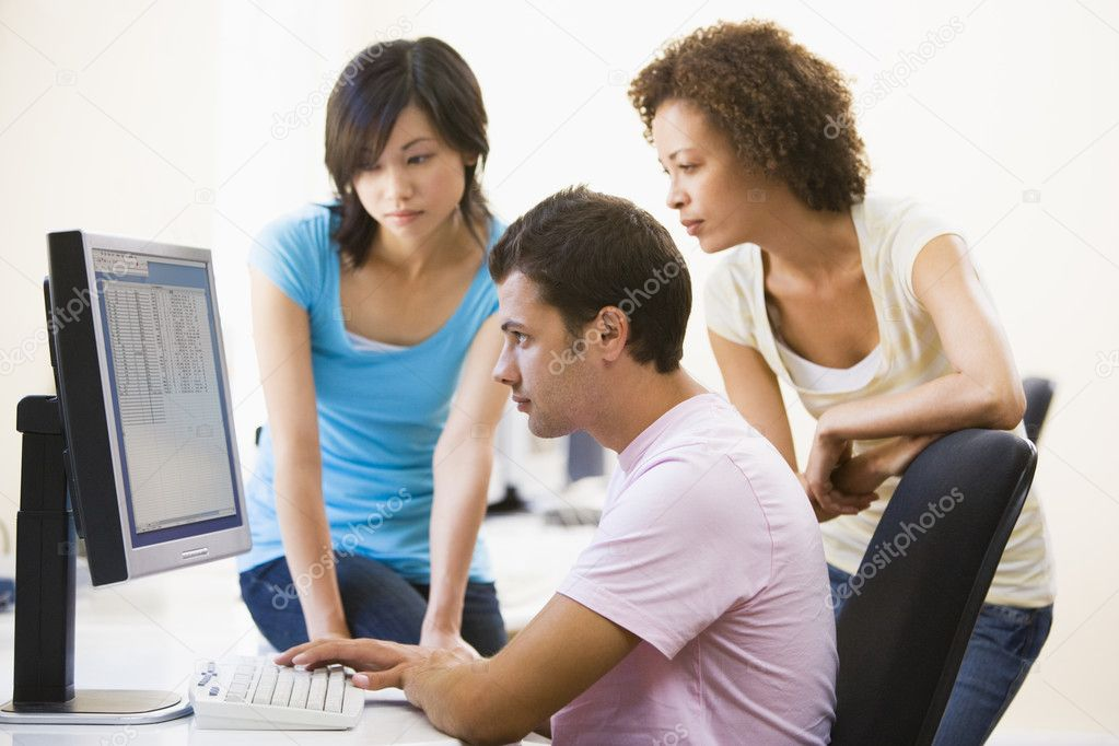 Three sitting in computer room looking at monitor — Stock Photo #4767305