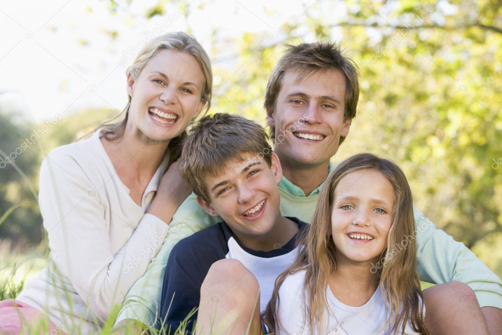 Family sitting outdoors smiling  Stock Photo #4767992
