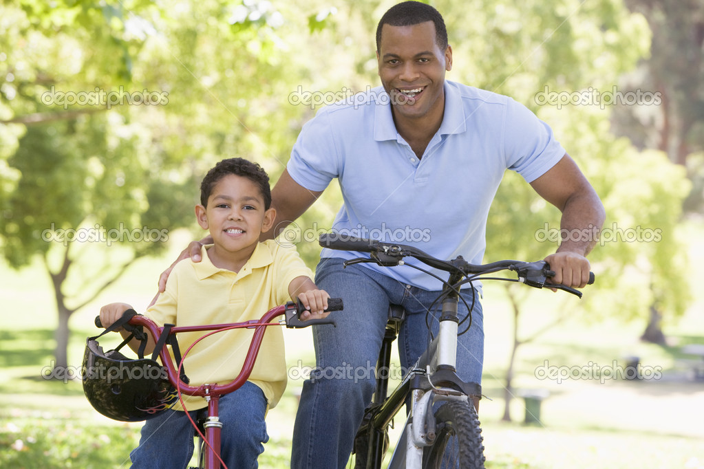Man and young boy on bikes outdoors smiling — Stock Photo #4768106