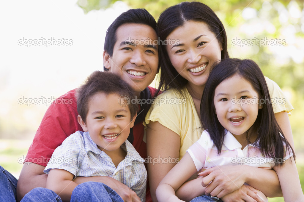 Family sitting outdoors smiling — Stock Photo #4768145