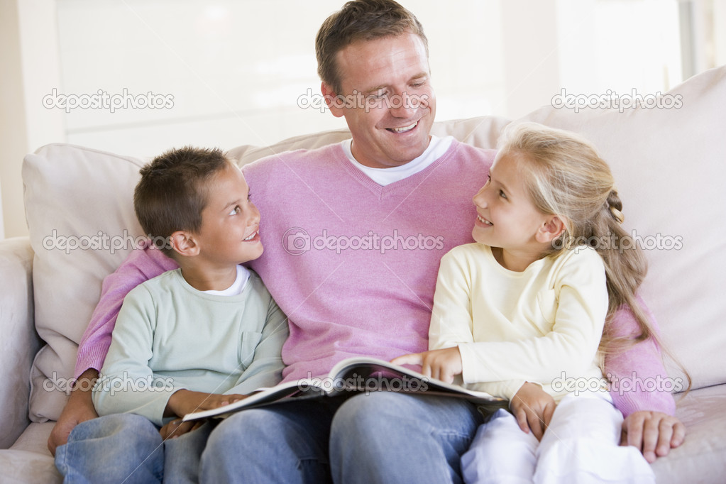 Man and two children sitting in living room reading book and smi — Stock Photo #4768279