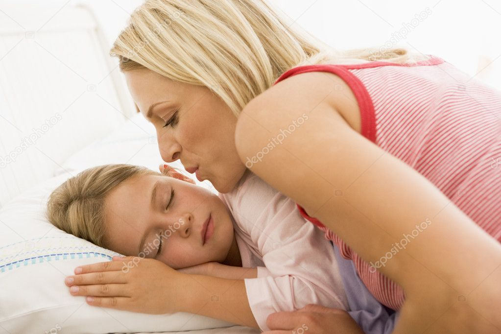 Woman Waking Young Girl In Bed With A Kiss Stock Photo
