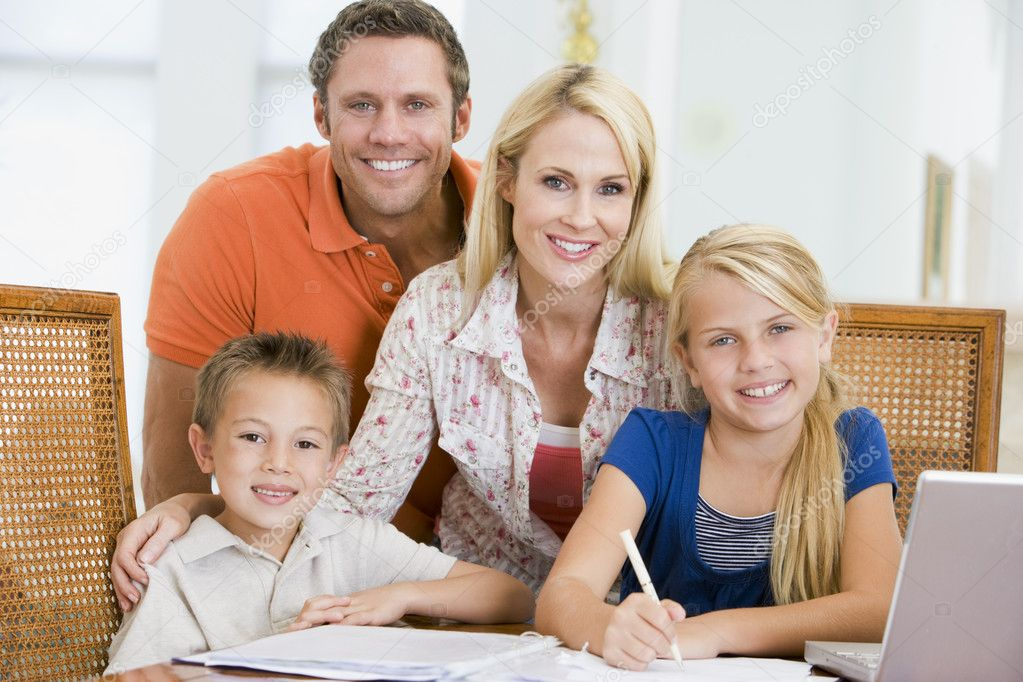 couple aider les deux jeunes enfants avec ordinateur portable faire ses devoirs dans le din. Black Bedroom Furniture Sets. Home Design Ideas