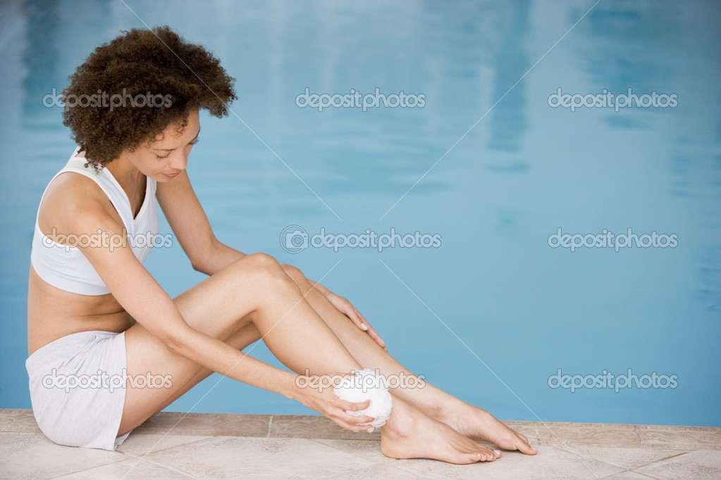 Woman sitting poolside using shower puff on leg — Stock Photo #4769136