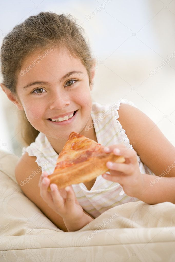 Young girl eating pizza slice in living room smiling — Stock Photo #4769974
