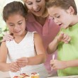 Woman with two children in kitchen decorating cookies smiling — Stock Photo