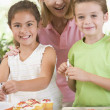 Woman with two children in kitchen decorating cookies smiling — Stock Photo #4770002