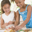 Two children in kitchen decorating cookies smiling - Stock Photo