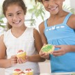 Stock Photo: Two children in kitchen decorating cookies smiling