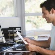 Man in home office using computer holding paperwork and smiling - Stock Photo